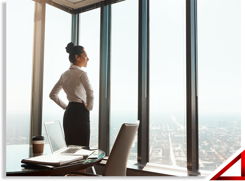 Woman looking out office window in highrise